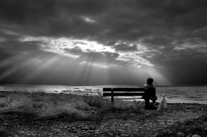 person sitting on a park bench looking at a coming storm