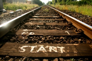 "railroad tracks leading into the distance with ""start"" painted on a tie"