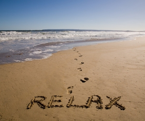 """beach with ocean and """"relax"""" drawn in the sand"""