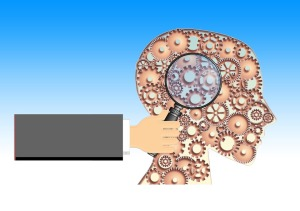 hand holding magnifying glass over brain, which is made up of gears