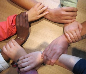 group of hands holding onto each other in a circle