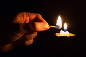 hand holding lit match, lighting a small candle