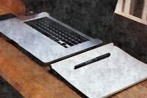 laptop with blank notebook and pen on a desk