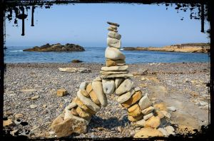 rocks piled in a balanced arrangement on a beach with the sea behind them