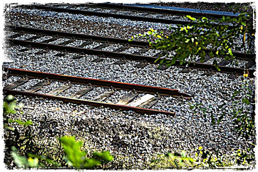 railroad tracks on a gravel bed, one of them ends in the gravel