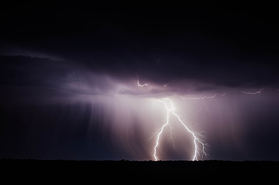 lightning striking the ground under dark clouds