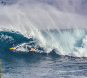 surfers coming out of the end of a tube