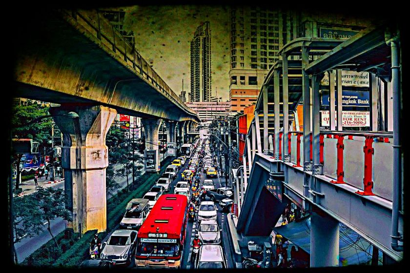 Bangkok traffic jam with cars and trucks and motorcycles all backed up below tram lines