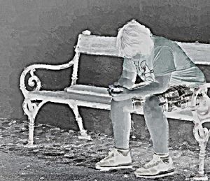 child with smartphone sitting on a bench