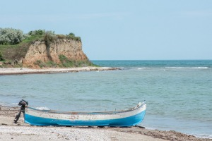 boat on beach with cliffs in the distance