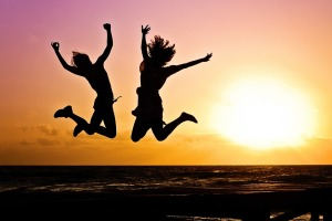 man and woman jumping for joy on a beach