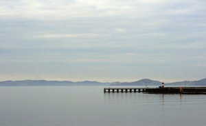 pier and lighthouse in distance across a lake