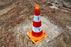 traffic cone standing on a muddy patch of ground