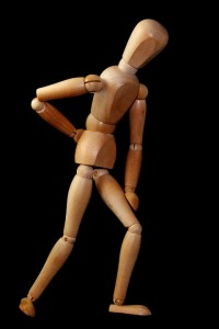 wooden figure slumped over with back pain