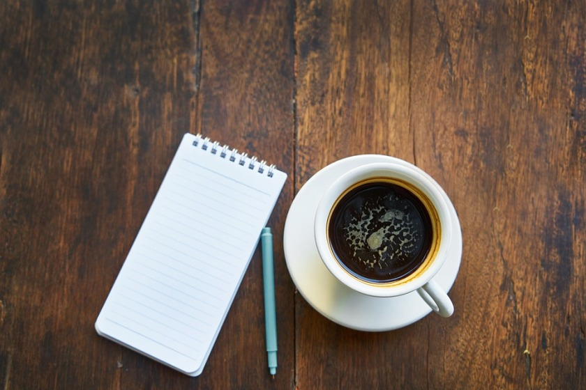 coffee and notepad and pen on a table